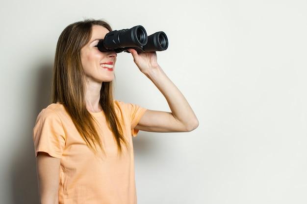 Молодая дружелюбная девушка в футболке смотрит в бинокль на светлом пространстве.