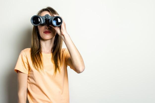 Молодая дружелюбная девушка, глядя через бинокль на светлом пространстве. баннер. эмоциональное лицо.