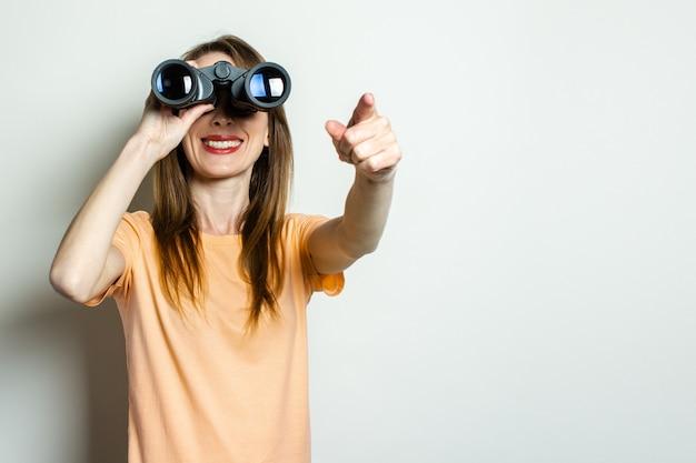 Молодая дружелюбная девушка смотрит в бинокль и указывает пальцем на что-то на светлом пространстве. баннер. эмоциональное лицо.