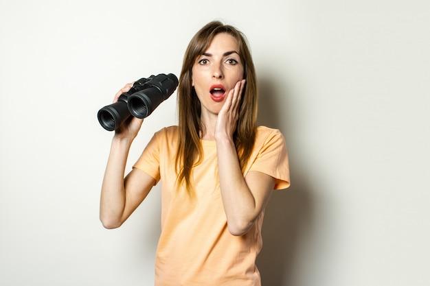 Молодая дружелюбная девушка с удивленным лицом в футболке держит бинокль на светлом пространстве. баннер. эмоциональное лицо.