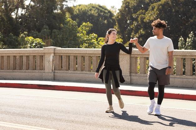 Молодые друзья на пробежке делают удар кулаком