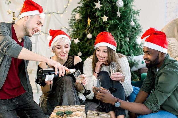 Юные друзья чокаются, пьют шампанское на рождество и новогоднюю вечеринку