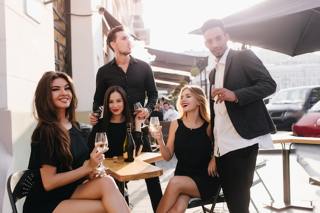 Юные друзья пьют шампанское на террасе