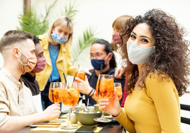 Young friends drinking cocktails wearing protective face mask