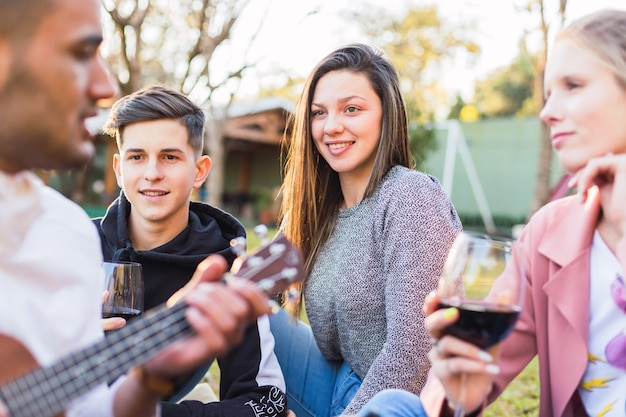Молодые друзья наслаждаются гитарной музыкой на открытом воздухе