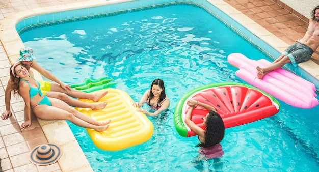 Young friends floating with air lilos inside swimming pool - happy people having fun on summer holidays vacation