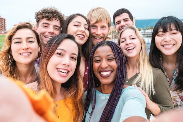 さまざまな文化や人種の若い友達が写真を撮り、幸せそうな顔を作る