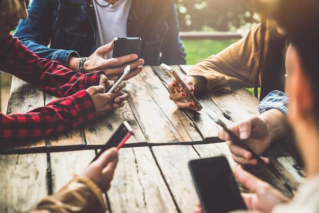 Группа молодых друзей, использующих мобильные телефоны на открытом воздухе - миллениалы подключают мобильные телефоны к wi-fi, сидя в баре-ресторане - социальные сети студентов вместе - технологическая концепция