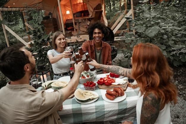 日没後、グランピングクリンキンググラスで夕食をとっている若い友人。電球のライトの下で野外ピクニックでキャンプする幸せな千年紀のギャング。アウトドアで友達と過ごす時間、バーベキューパーティー