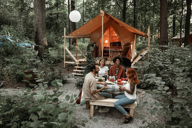 Young friends having dinner at glamping talking, laughing after sunset. happy millennial gang camping at open air picnic under bulb lights. spending time with friends outdoors, barbeque party