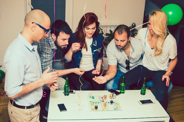Молодые друзья, имеющие фу на вечеринке с настольными играми