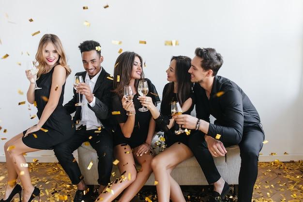 Молодые друзья веселятся и пьют шампанское на вечеринке