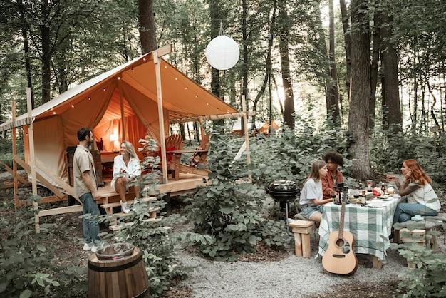 日没後のグランピングを楽しんでいる若い友達。電球のライトの下で野外ピクニックで幸せな若者のギャングミレニアルキャンプ。バーベキューパーティーでワインを飲む男と女との友情の概念