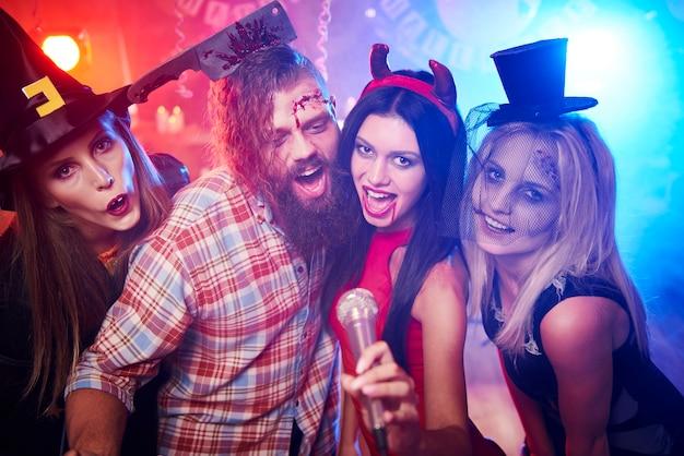 ハロウィーンパーティーで楽しんでいる若い友達 無料写真