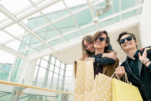 Юные друзья веселятся в торговом центре