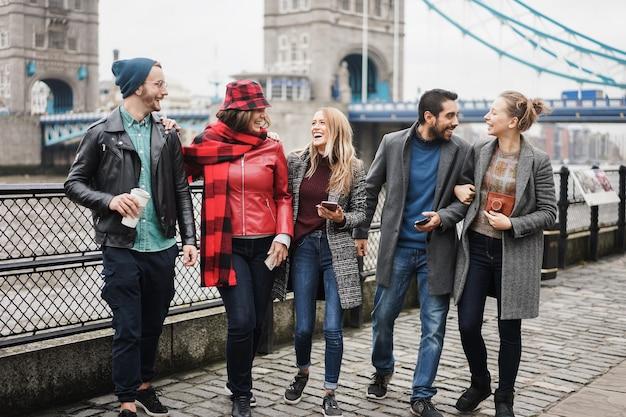 ロンドンのタワーブリッジを背景に街でアウトドアを楽しんでいる若い友達-中央の女の子の顔に焦点を当てる