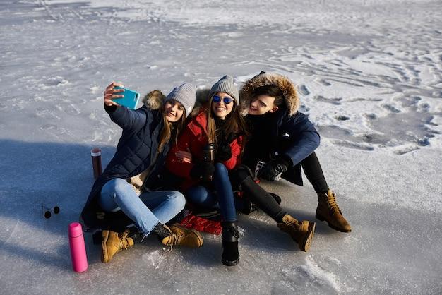 Молодые друзья веселятся на свежем воздухе зимой