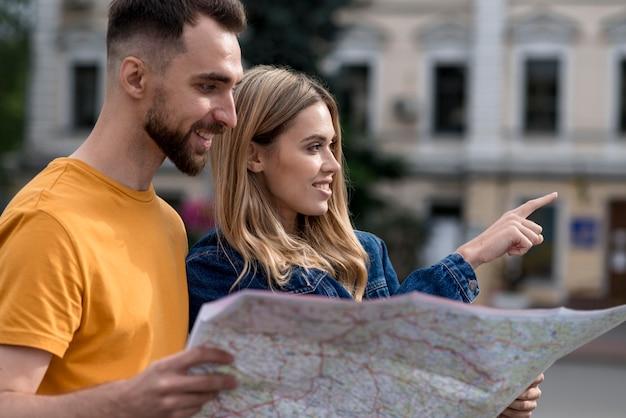 Молодые друзья держат карту и указывают направления