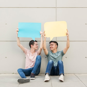 Young friends holding colorful speech bubbles