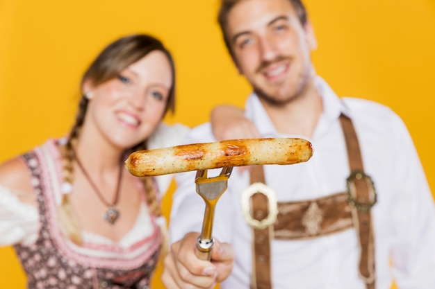 Young friends holding grilled sausage