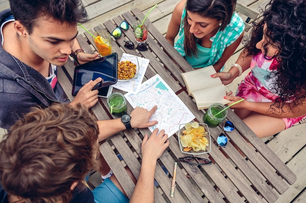 Young friends looking map over a wooden table with healthy drinks and snacks. holidays and tourism concept.