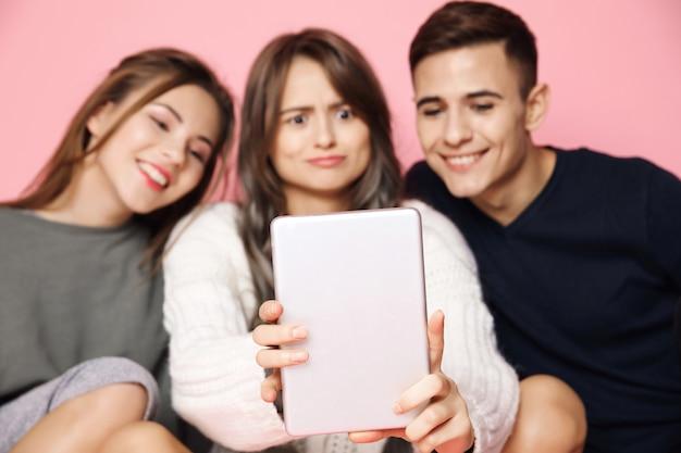 Молодые друзья, делающие селфи на планшете на розовом