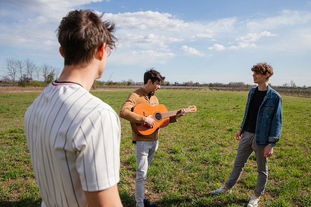 Young friends meet in a meadow in the open air with a guitar and sing songs - male friendship and passion for music concept - focus on guitar.