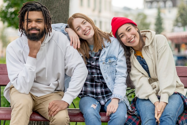 Young friends outdoor sitting on bench