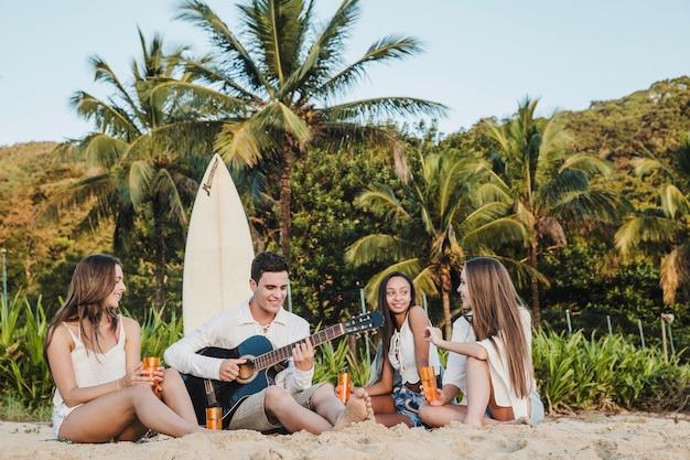 Молодые друзья играют на гитаре на пляже