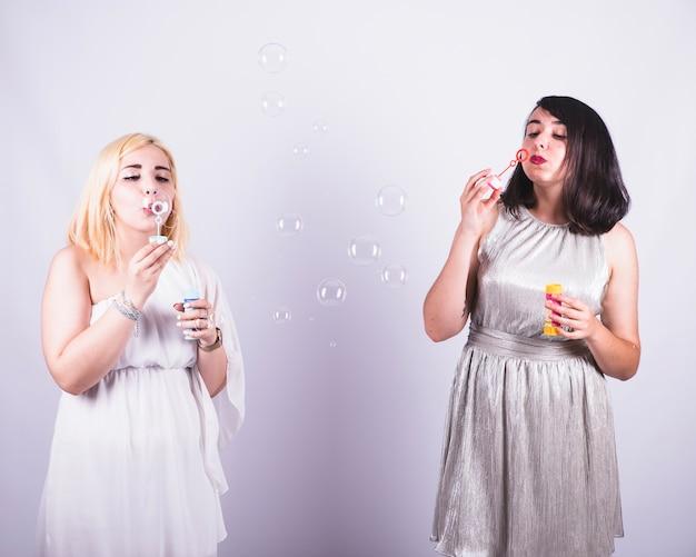 Молодые друзья играют с пузырьками