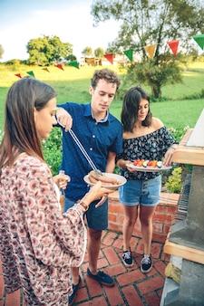 야외 여름 파티에서 바비큐 요리를 위해 소시지와 야채 꼬치를 준비하는 젊은 친구들