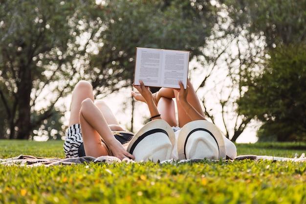 若い友達は屋外で本を読みます。横になって本を読んでいる友達。帽子をかぶった2人の友人が公園で本を読んだ。友情とリラクゼーションの概念。