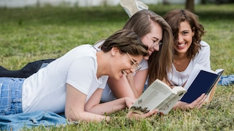 Young friends reading lying on park lawn