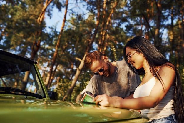 森の中の現代の緑のジープのボンネットにある地図を読んでいる若い友人。
