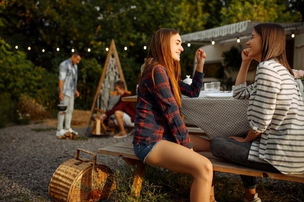 Юные друзья отдыхают на пикнике в кемпинге в лесу. молодежь в летнем путешествии на внедорожнике, в машине для кемпинга две пары отдыхают, путешествуют с прицепом