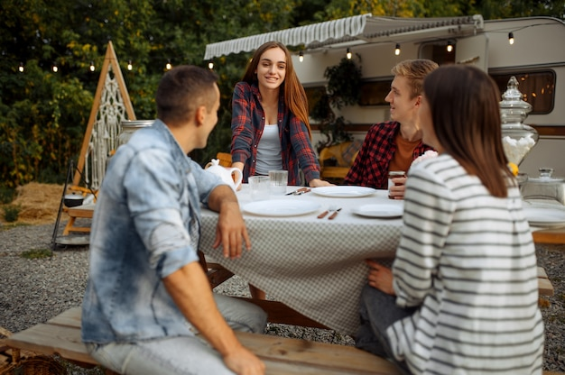 Young friends relax on picnic at camping in the forest