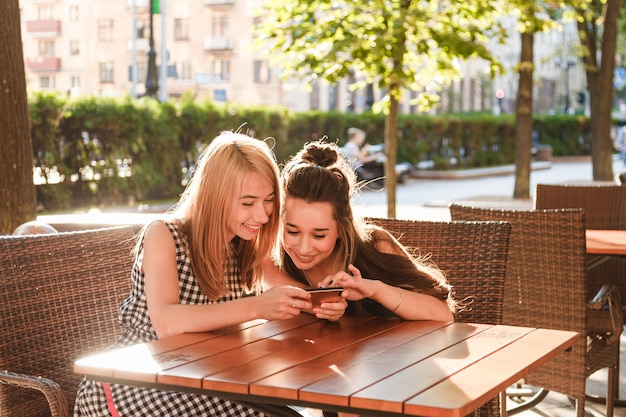 Young friends sitting in a cafe looking at smartphone.