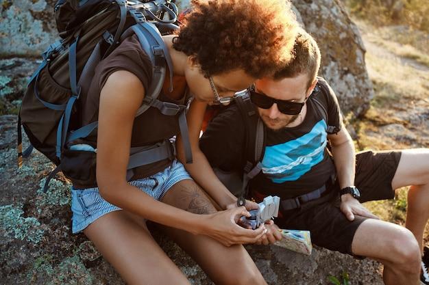 Молодые друзья сидят на скале в каньоне, глядя на компас