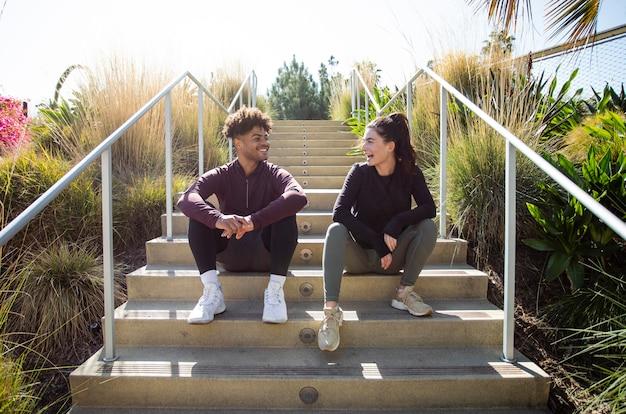 Молодые друзья, сидя на лестнице