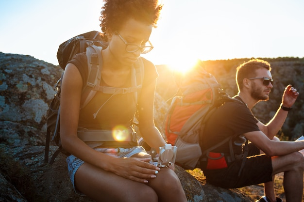 Young friends sitting on rock in canyon, looking at compass