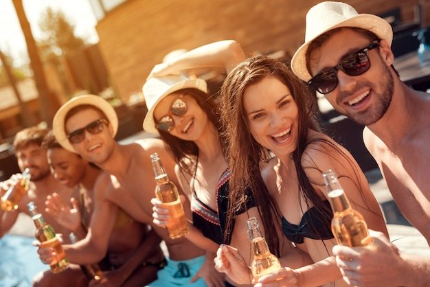 Young friends smile with alcoholic drinks at poolside