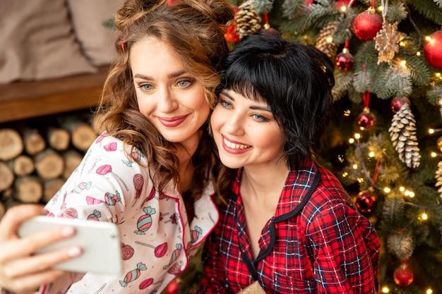젊은 친구들이 크리스마스 이브에 자화상을 찍습니다. 장식 된 크리스마스 트리 근처에서 잠옷을 입고 앉아보세요.