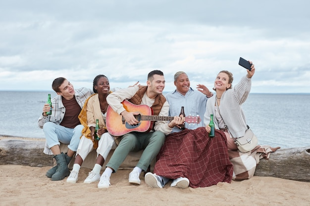 Young friends taking selfie at beach party