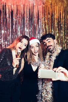 Giovani amici che prendono selfie per i partiti nuovi anni