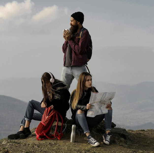 Young friends travelers bearded man hipster and two pretty girls women with map explore route outdoors on mountain top on foggy sky