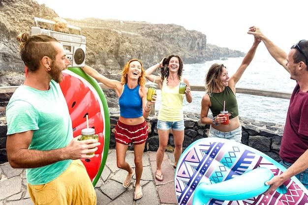 旅行場所の自然なプールで楽しんでいる若い友人の行楽客-代替のビーチパーティーで踊ったりカクテルを飲んだりする幸せな千年紀の人々-暖かいフィルターのワンダーラストライフスタイルコンセプト