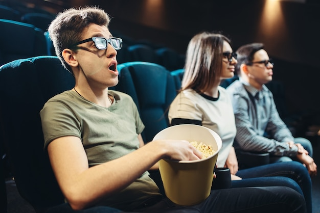 Young friends watching 3d movie in cinema together. showtime, entertainment industry technologies
