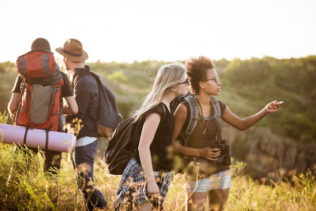 Young friends with backpacks enjoying view, traveling in canyon