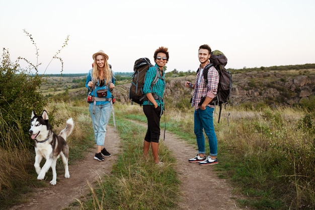Young friends with backpacks and huskies smiling, traveling in canyon