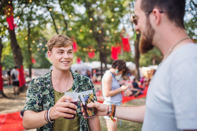 Young friends with drinks at a summer festival, clinking glasses.